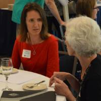Two alumnae talking at a table
